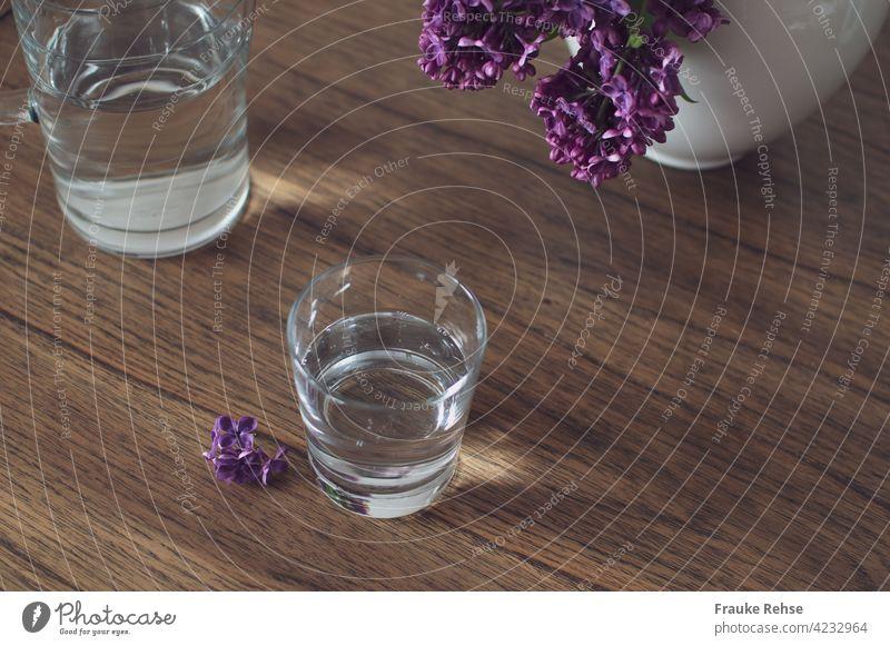 Glas und Glaskaraffe mit Wasser auf einem Holztisch mit Flieder in der Vase Wasserglas Karaffe trinken Durst Erfrischung Gesundheit kalt Durstlöscher Getränk