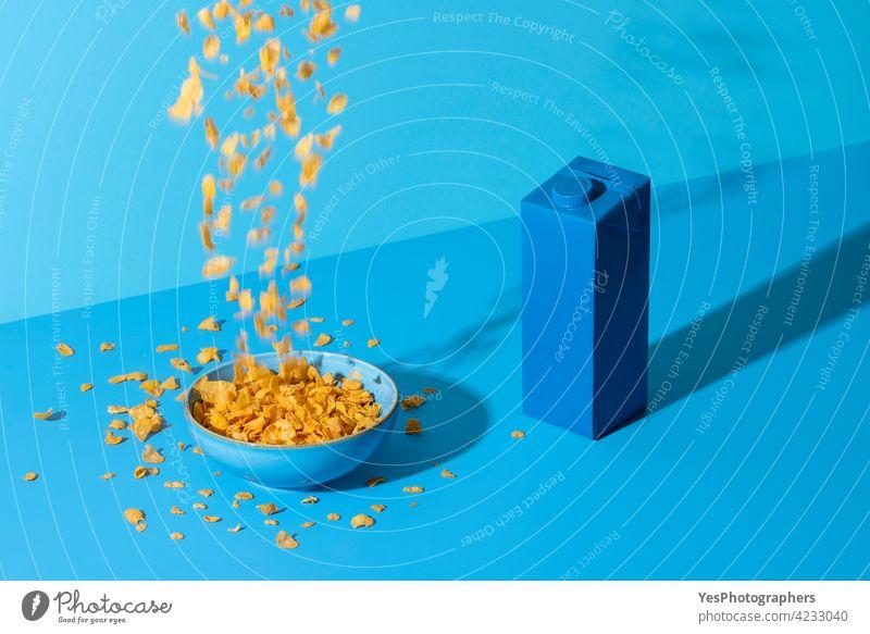 Pouring Cornflakes Müsli in einer Schüssel auf einem blauen Tisch. Frühstückstisch in natürlichem Licht. abstrakt Unfall Hintergrund Flasche Schalen & Schüsseln