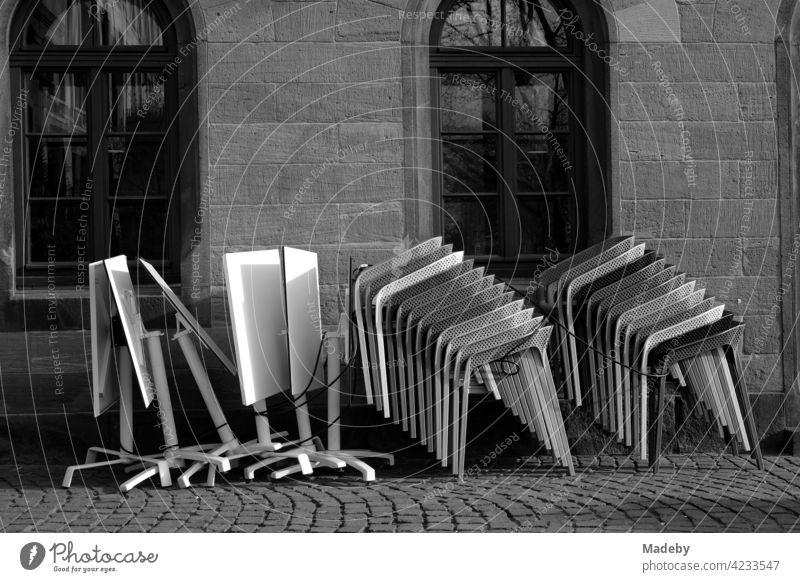 Gestapelte Designerstühle und zusammengeklappte Tische vor einem alten Café auf dem Römerberg in Frankfurt am Main in Hessen, fotografiert in neorealistischem Schwarzweiß