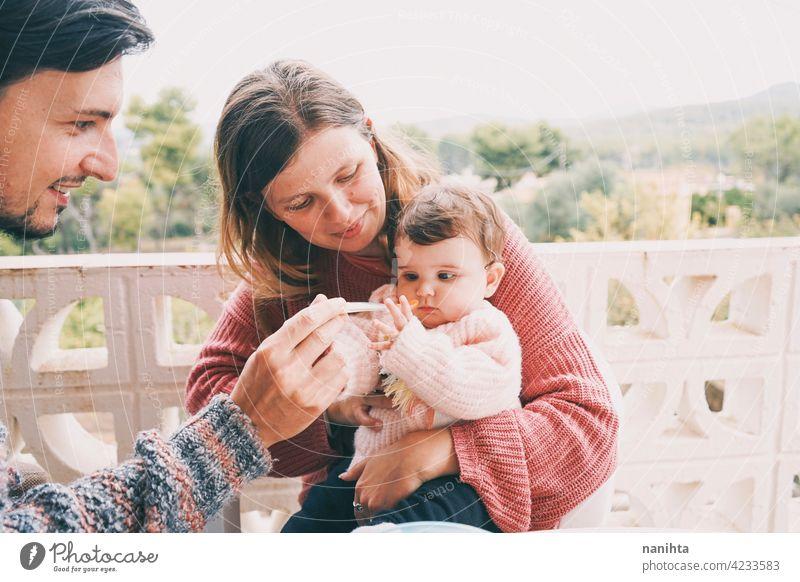 Echte Familie teilt das erste Essen ihres Babys wirklich Lebensmittel Zusammensein Beikost Mama Papa Kinderbetreuung füttern Püree Sahne im Freien