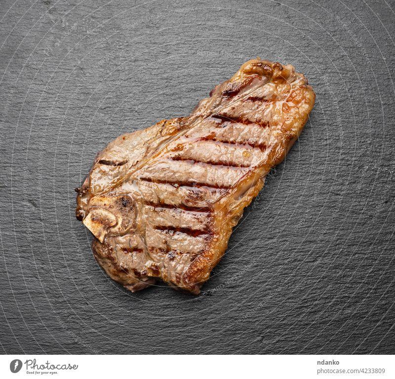 ganzes gebratenes New Yorker Rindersteak auf einem schwarzen Brett, Striploin-Doneness rare oben Barbecue grillen Rindfleisch blutig Holzplatte braun gekocht
