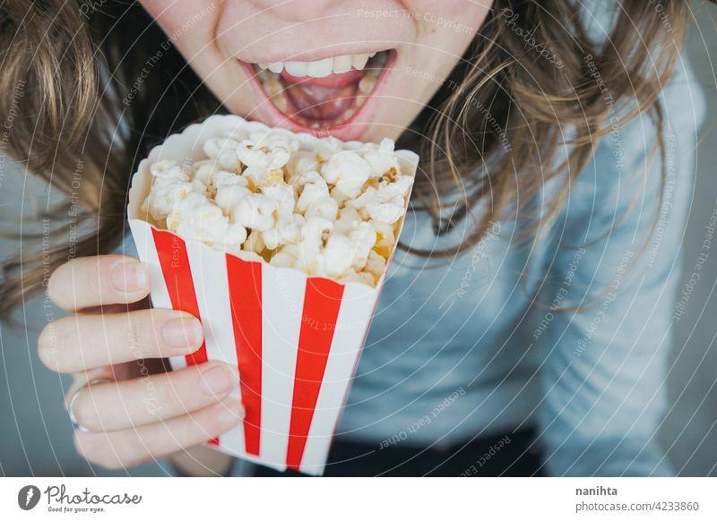 Frau hält einen Behälter voll mit Popcorn Mais Kino Filmmaterial altehrwürdig retro klassisch stilvoll rot weiß Versuchung Snack genießen Hand Lifestyle Leben