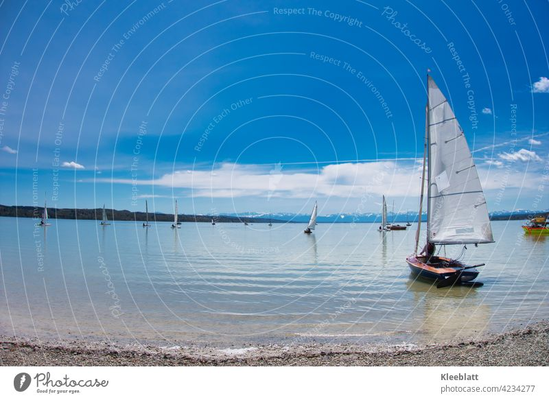 Segelboote werden am Ammersee zu Wasser gelassen - Auszeit und Erholung bei schönem Frühlingswetter Berge Himmel blau zahrte Wolken klares Wasser Sport