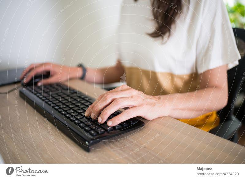 Nahaufnahme einer Frau, die zu Hause arbeitet. Hände auf der Tastatur und ein sauberer Schreibtisch Job pc Keyboard Tippen Hand Business Büro 40-50 Erwachsener