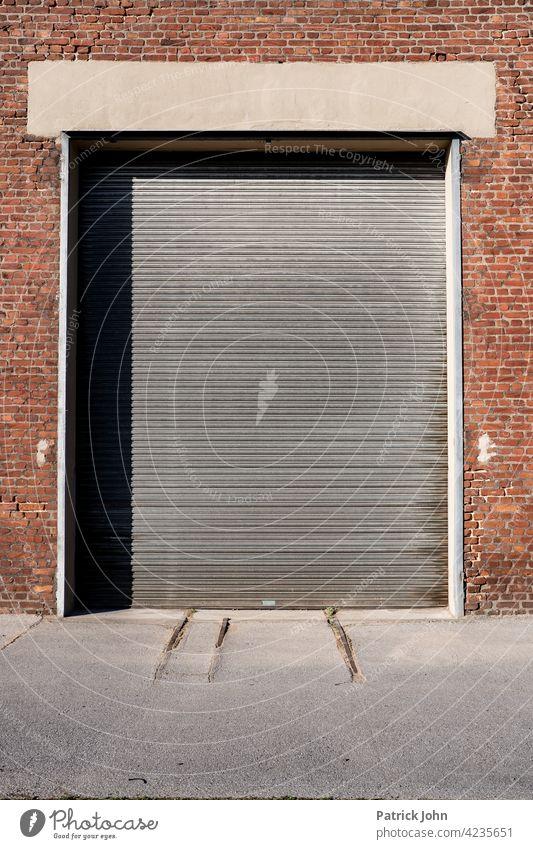 Rolltor in einer alten Industriehalle aus Bachstein. Tor Garagentor Fassade Lastkraftwagen Baustein Menschenleer Gebäude zugeklappt Lagerhalle Einfahrt