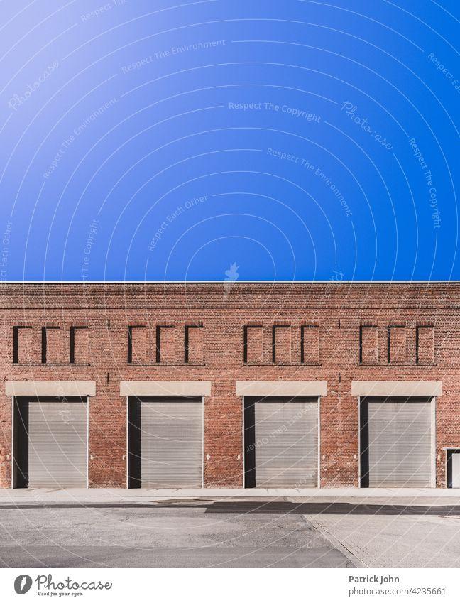 Rolltor in einer alten Industriehalle aus Bachstein. Tor Garagentor Fassade Lastkraftwagen Menschenleer Gebäude Lagerhalle Einfahrt Außenaufnahme Blauer Himmel