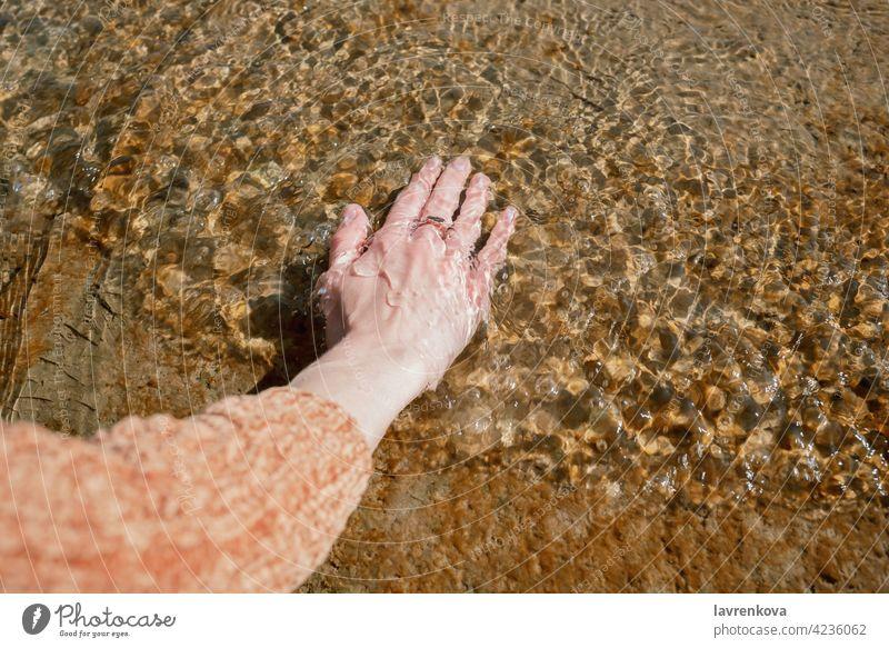 Hand der Frau im kalten Wasser auf einem Steg gesichtslos Strand Pier berührend Element Sauberkeit übersichtlich Pullover Rippeln Natur im Freien friedlich See