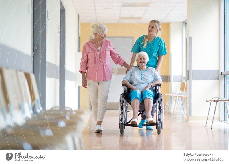 Ältere Frau im Rollstuhl mit ihrer Tochter und Krankenschwester rollstuhl Behinderung körperliche Beeinträchtigung Behinderte Mobilität abstützen Zugänglichkeit