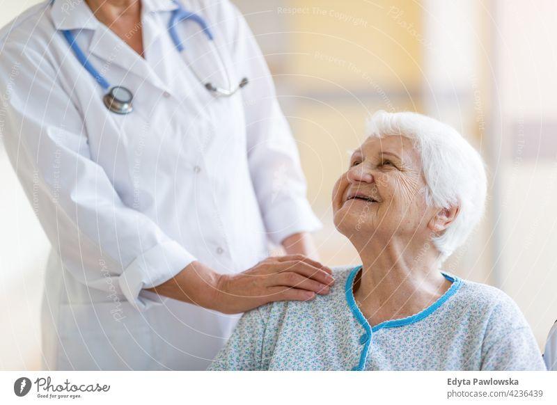 Ältere Frau im Rollstuhl mit Arzt im Krankenhaus rollstuhl Behinderung körperliche Beeinträchtigung Behinderte Mobilität abstützen Zugänglichkeit Objekt Rad