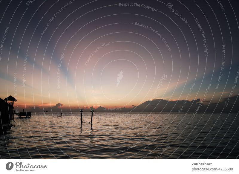 Sonnenuntergang mit goldenen Sonnenstrahlen am Himmel über einer Lagune auf den Malediven Abend Abendrot Wolken Sonnenlicht Meer Horizont Dämmerung Urlaub