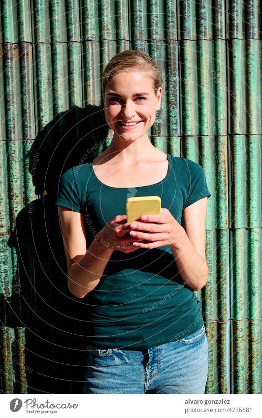 Junge attraktive Frau, die ein Smartphone benutzt und direkt in die Kamera schaut schön jung Erwachsener Mobile Model Funktelefon Glück Telefon che Person