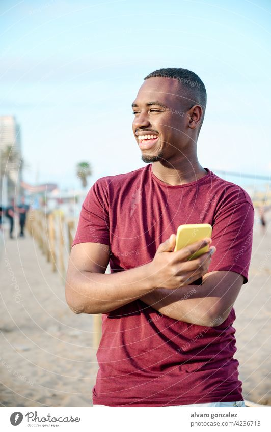 junger schwarzer Mann am Strand lächelnd und mit seinem Smartphone Afrikanisch männlich Amerikaner Erwachsener Porträt Model Funktelefon gutaussehend lässig