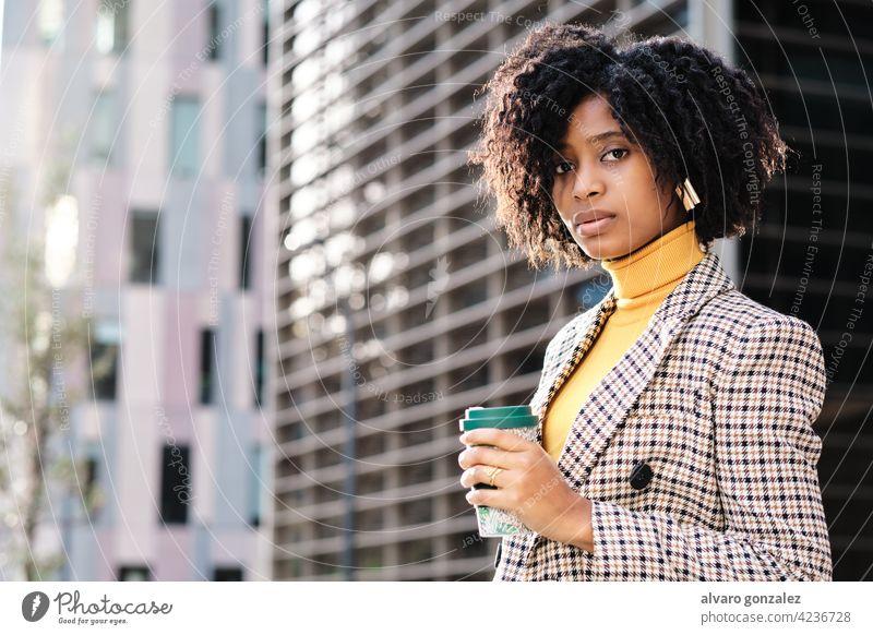 Geschäftsfrau hält eine Tasse Kaffee im Freien. Afro-Look Business Frau urban Großstadt finanziell Revier Straße Unternehmer Porträt professionell selbstbewusst