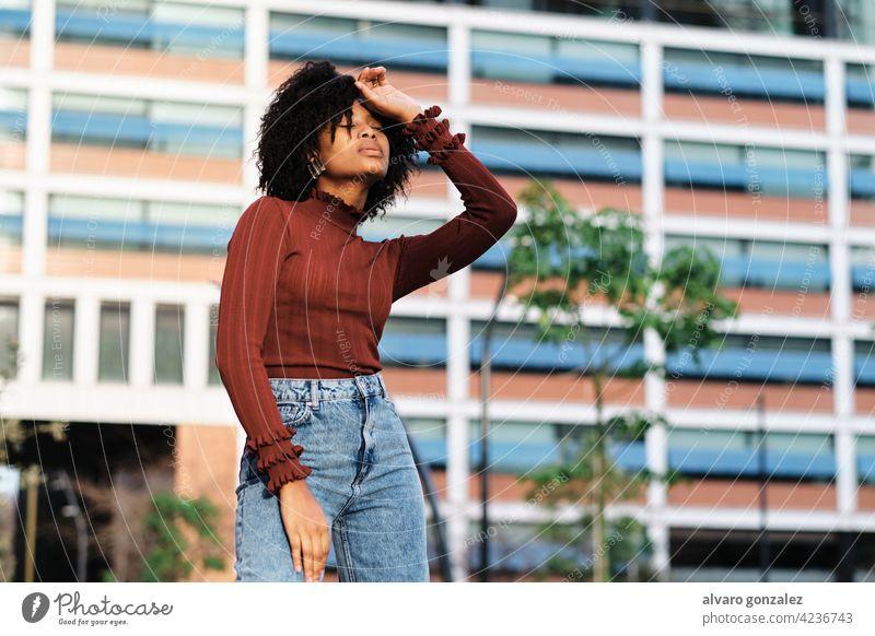 Afro-Frau steht im Freien auf der Straße. jung Afro-Look schwarz urban Porträt Mode Großstadt lockig Behaarung laufen Kleidung außerhalb Hintergrund Stil