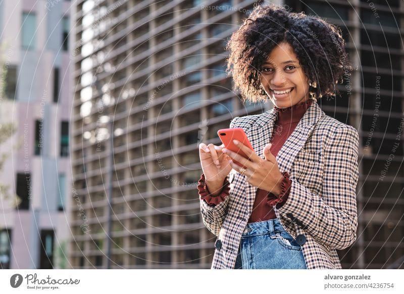 Geschäftsfrau beim Senden von Nachrichten auf ihrem Telefon. Business Frau Afro-Look Mobile finanziell Revier Großstadt urban im Freien professionell Straße
