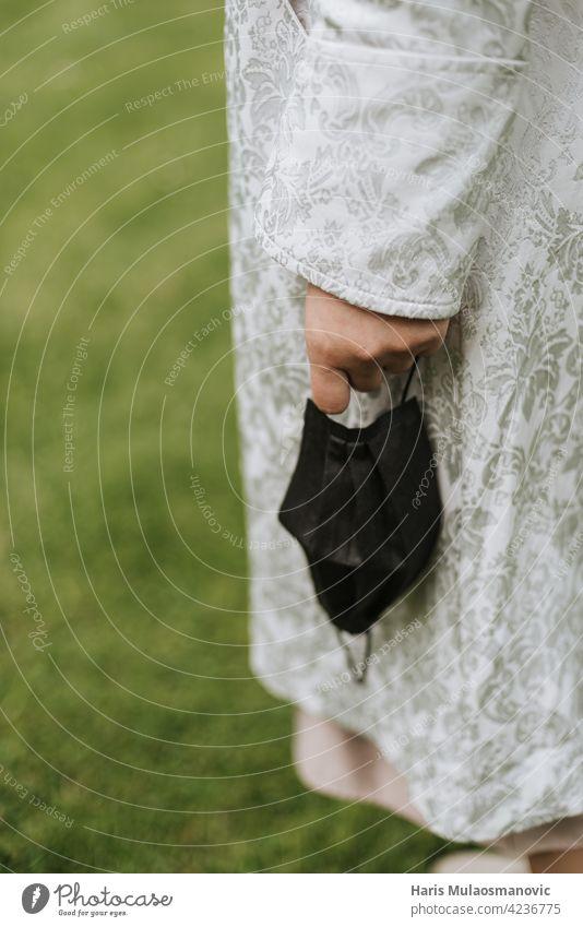 hält Gesichtsmaske in der Hand Nahaufnahme im Freien in der Natur 2019-ncov Pflege abschließen Stoff Corona-Virus Coronavirus Bund 19 covid-19 Krankheit Arzt