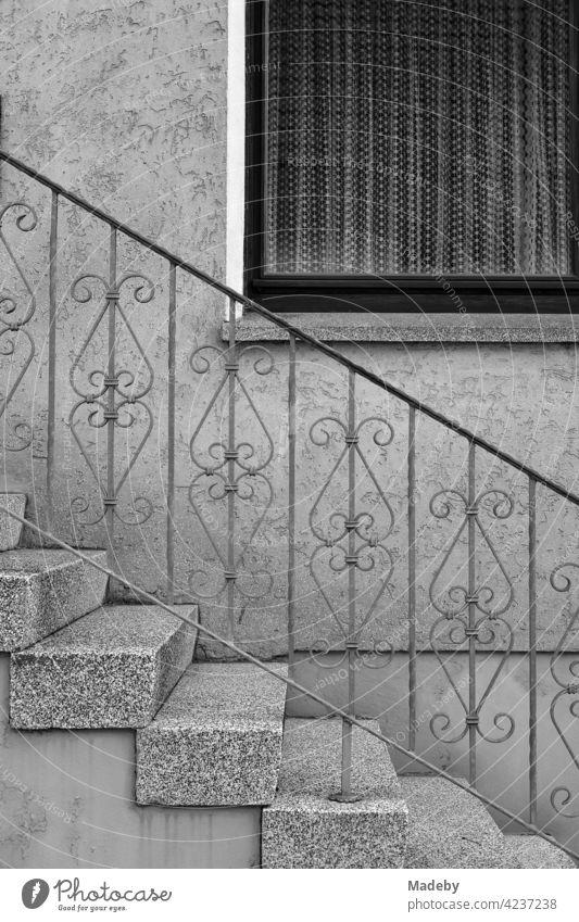Spießeridylle mit Treppengeländer aus Schmiedeeisen und Gardinen hinter dem Fenster eines Wohnhaus in Oerlinghausen bei Bielefeld im Teutoburger Wald in Ostwestfalen-Lippe, fotografiert in klassischem Schwarzweiß