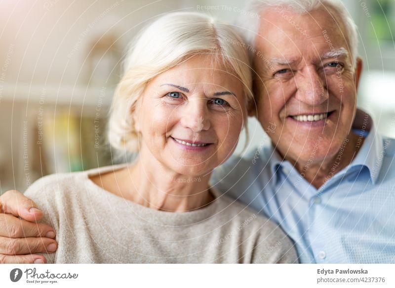 Glückliches älteres Paar, das sich in seinem Haus umarmt im Innenbereich im Inneren heimwärts Appartement Küche Frau Liebe Menschen Zusammensein zwei Senior