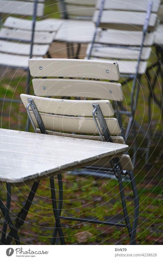 Gartenstuhl im Regen, zusammengeklappt Stuhl nass Biergarten biergartengarnitur biergartenmöbel Tisch Gartentisch stühle draußen Gastronomie Menschenleer