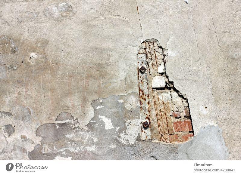 Hauswand mit wenig Farbe Mauer Putz Stein Loch Beschädigung Reparatur alt Fassade trist grau kaputt Außenaufnahme Verfall Menschenleer
