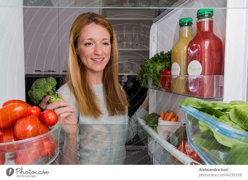 Offener Kühlschrank von innen, Glasregale mit buntem Gemüse, Flaschen mit Bio-Säften. Junge Frau mit glücklichem Lächeln nimmt Brokkoli. Gesunde Ernährung, veganes Konzept.