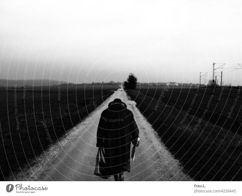 Heimkehr Frau Dorf Feldweg gehen Hut Mantel gebeugt Handtasche Felder Degersen Montage Einsamkeit einsam traurig Traurigkeit Mensch allein Fotomontage Trauer