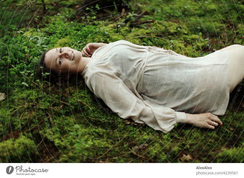 Junge Frau liegt auf Moos im Wald auf einer Lichtung Junges Fräulein Boden Waldboden schoen anmutig brünett hübsch 18-30 Jahre 30-45 Jahre langhaarig kleid