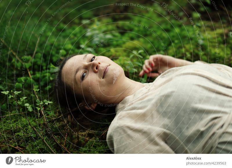 Junge Frau auf Moos in Waldlichtung liegend Boden Waldboden hübsch zierlich brünett 18-30 Jahre 30-45 Jahre langhaarig Kleid Pflanzen Natur Sträucher Zweige