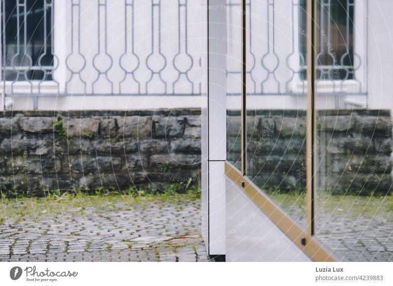 Durchsicht und Spiegelung: Schaufenster, Kopfsteinpflaster, Mauer, Zaun und Fenster Glasscheibe Form Licht Reflexion & Spiegelung Stadt Scheibe Gebäude