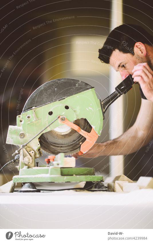 Handwerker konzentriert an der Kappsäge Heimwerker Holz aufmerksam Säge sägen Schreiner Beruf Werkzeug Arbeit & Erwerbstätigkeit Baustelle heimwerken Mann