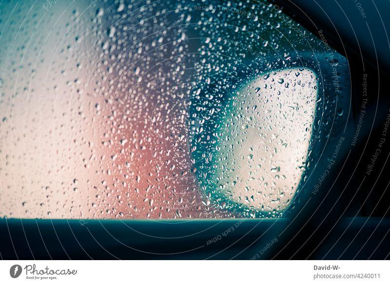 Regentropfen auf einer Scheibe eines Autos Regenwetter schlechtes Wetter Autoscheibe Unwetter Straßenverkehr Herbst nass Wassertropfen PKW Autospiegel