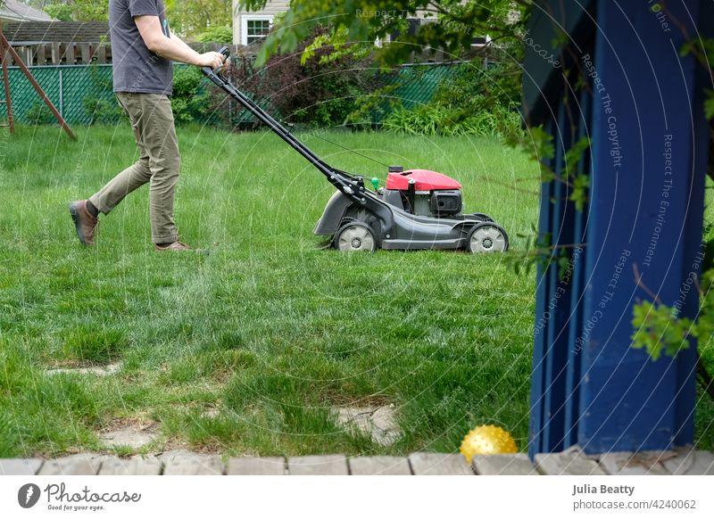 Mann mäht hohes Gras; Vorstadt-Hinterhof mit Terrasse und Landschaftsbau Rasen Mäher Rasenmäher hoch Wachstum Arbeit Wochenende Übung heimwärts Schiffsdeck Holz