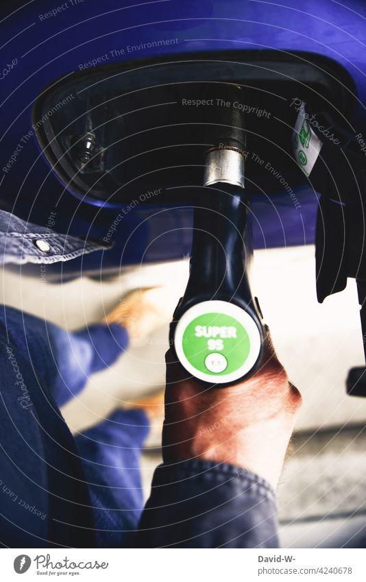 Mann tankt sein Auto Tankstelle tanken Zapfsäule Benzin Rohstoffe & Kraftstoffe PKW benzinpreis Sprit teuer