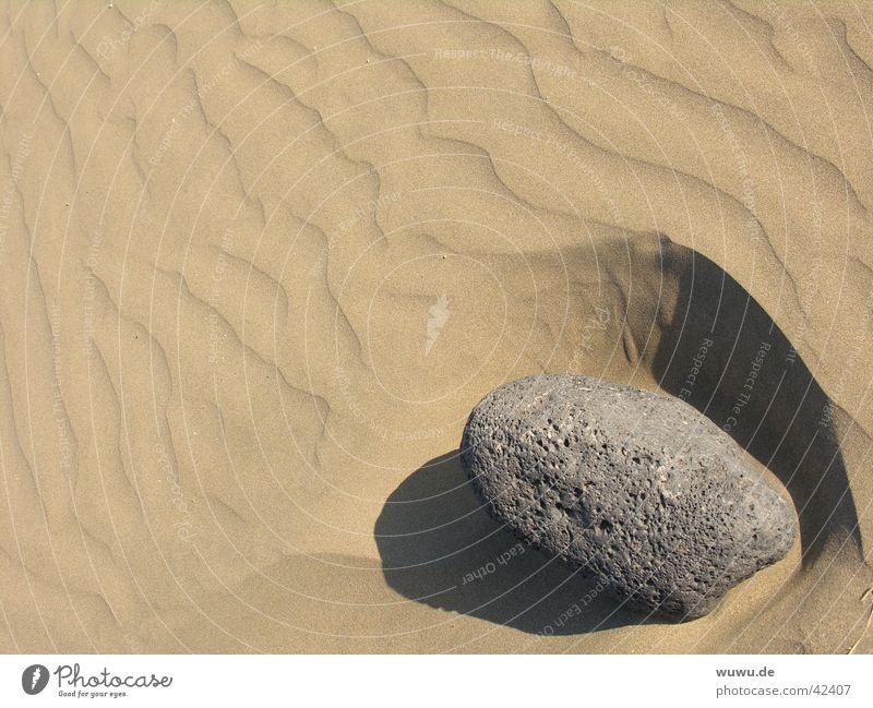 Stein im Sand Furche grau beige Wüste Schatten Fremdkörper