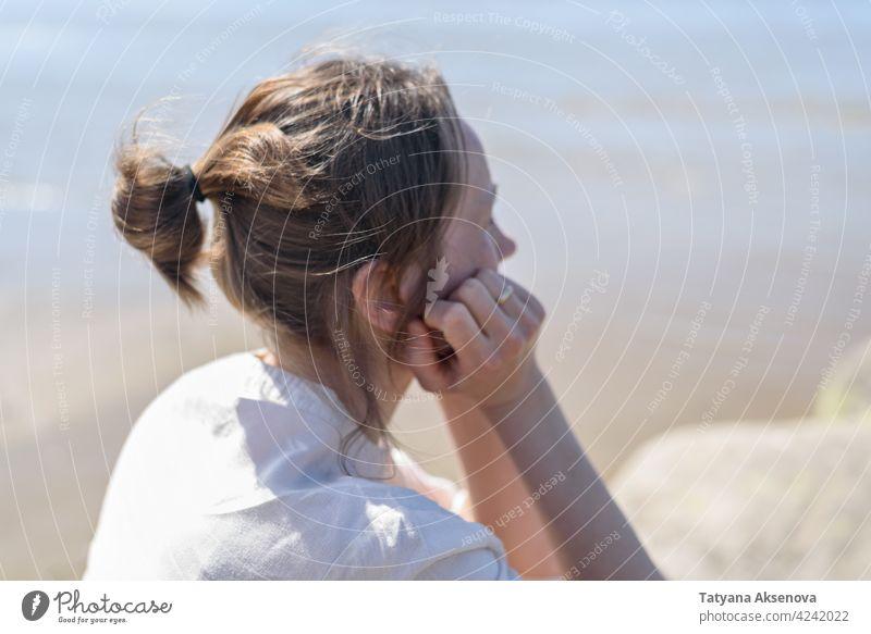 Frau sitzt in der Nähe von Meer, Blick zum Wasser Natur im Freien Wohlbefinden Erholung Achtsamkeit sich[Akk] entspannen Atmung MEER Ruhe Meditation Person
