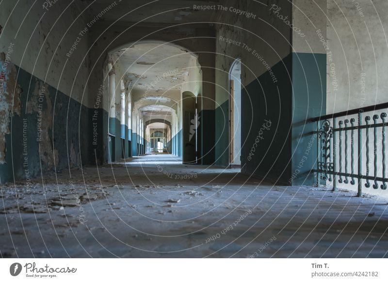 ein langer Flur in dem die Zeit stehen geblieben ist empty Ruine verfallen Tür alt Gang Licht Gebäude kaputt beelitz Vergänglichkeit Farbe Architektur Farbfoto