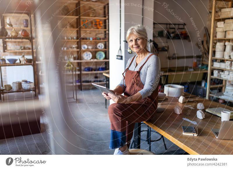 Ältere Handwerkerin mit Tablet-Computer im Kunstatelier Töpferwaren Künstler Keramik Arbeit arbeiten Menschen Frau Senior Erwachsener lässig attraktiv Glück