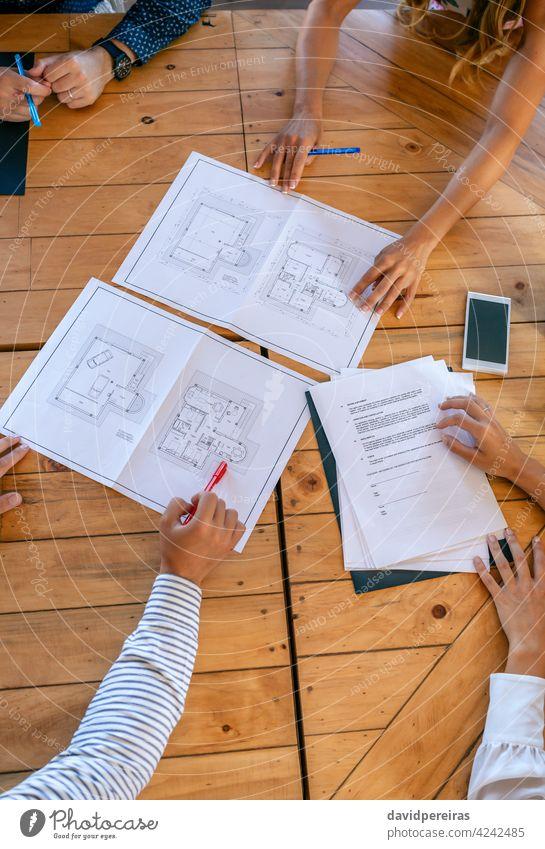 Unbekannte Architekten in einer Arbeitsbesprechung bei der Betrachtung von Bauplänen für ein Haus Antenne Architektur Arbeitstreffen unkenntlich Zeigen Teamwork