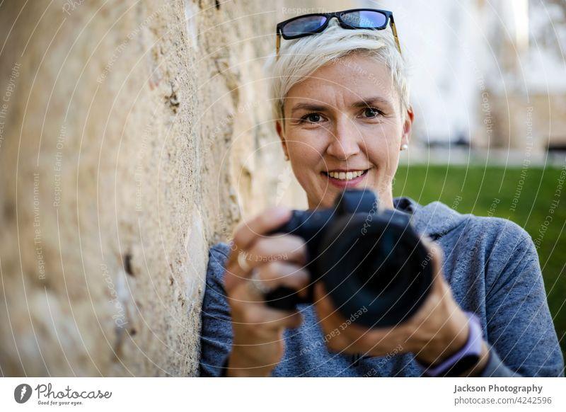 Lächelnde Frau mit der Digitalkamera in ihren Händen Porträt Fotograf Fotokamera alt Textfreiraum Kapuzenpulli Brille positiv Mädchenfotograf Fotografieren