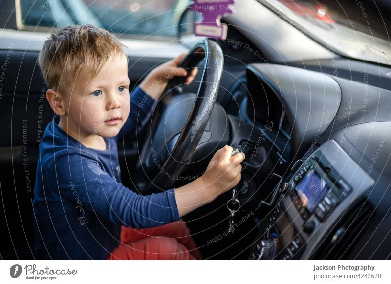 Kleiner Junge sitzt am Lenkrad des Autos PKW Laufwerk Spaß Kleinkind Verkehr Gesicht blond 3-4 Vorschule Fenster Straße lenken Sitz im Freien Familie lustig