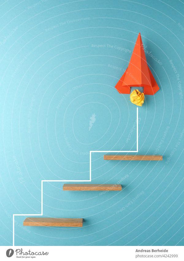Orangefarbene Rakete oder Raumschiff, das die Treppe hinaufsteigt, Aufschwung oder Startup-Konzept zerknittert Papier Ball Inbetriebnahme Aktion Tor Erfolg