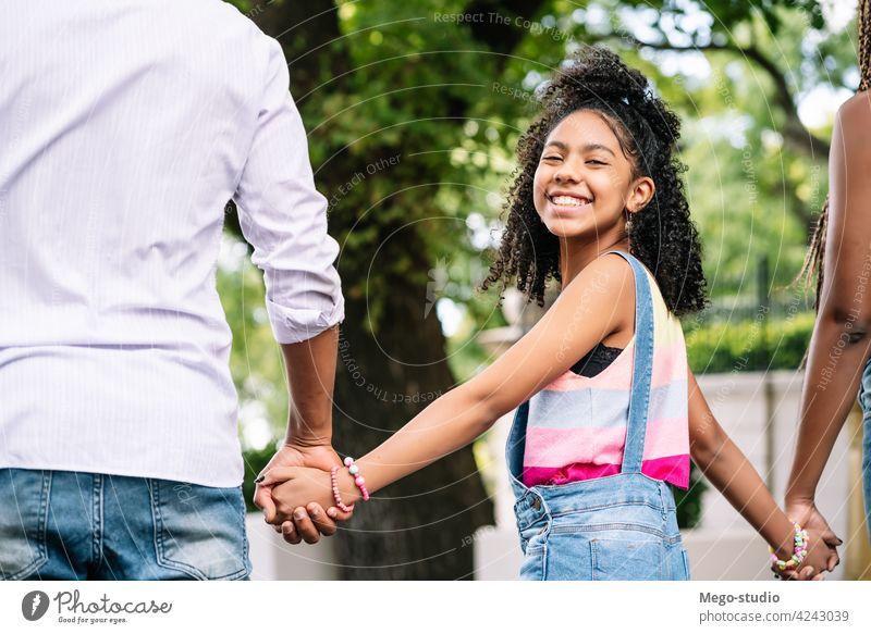 Kleines Mädchen genießt einen Spaziergang im Freien mit ihren Eltern. Familie Zusammensein Großstadt Straße urban Glück laufen Mutter Vater Tochter drei Tag