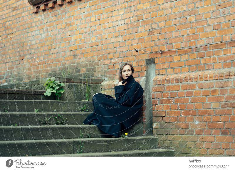 die Frau sitzt in einen Mantel gehüllt auf einer Treppe und blick über die Schulter den Weg zurück Junge Frau Melancholie Frauengesicht feminin langes Haar
