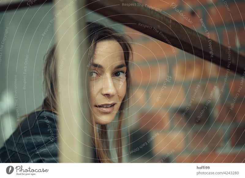 die junge Frau blickt lächelnd in die Kamera Junge Frau lächelnde Frau Frauengesicht feminin Blick in die Kamera ästhetisch Gesicht trendy langhaarig natürlich