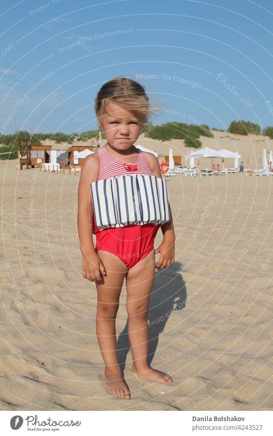 kleines Mädchen steht am Strand in einem speziellen Badeanzug für Kinder, die nicht schwimmen können. Kind im Badeanzug, den er über Wasser hielt Porträt