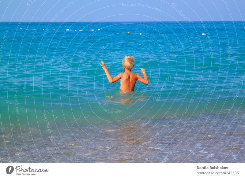 Junge geht sanft mit seinen Händen in das kalte Sommermeer MEER Wasser Kind Lifestyle springen platschen Glück Kinder Spaß werfen Truthahn Menschen Urlaub