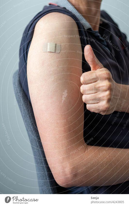 Mann mit einem Heftpflaster auf dem Arm und Daumen hoch Impfung coronavirus Vorbeugung Gesundheit Virus Pandemie Coronavirus Krankheit Prävention Medizin Grippe