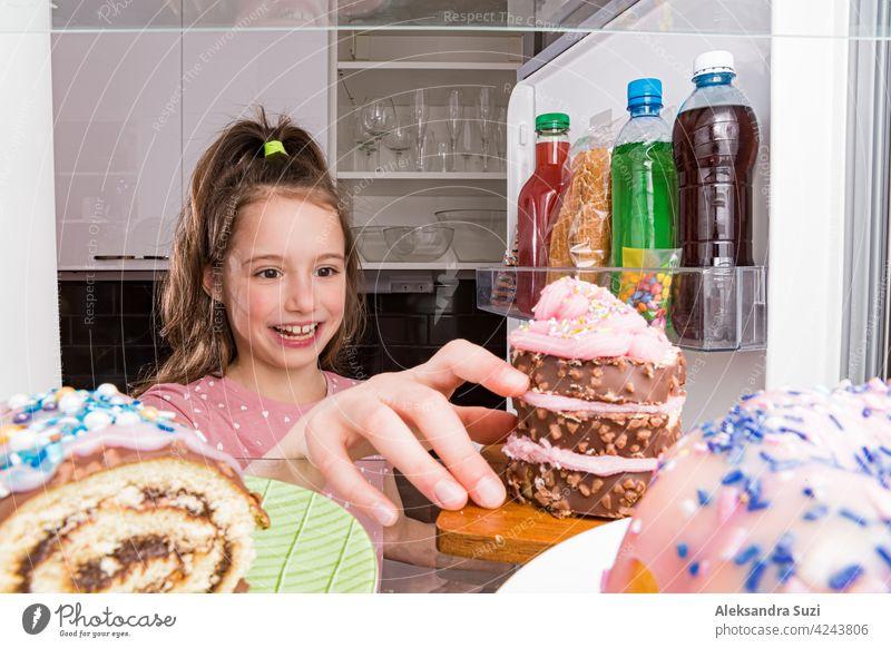 Öffnen Sie den Kühlschrank von innen, Glasregale mit bunten Desserts, Kuchen, Kekse, Süßigkeiten, Flaschen mit Zucker Getränke. Ungesunde Ernährung, Zucker Lebensmittel Konzept. Kleines Mädchen mit glücklichen Lächeln unter Kuchen