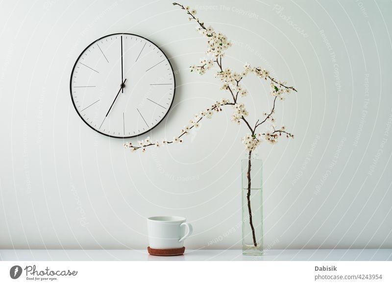 Wanduhr, blühender Zweig und Tasse auf weißem Hintergrund Uhr Dekor Blume sehr wenige Schreibtisch Raum Desktop heimwärts Attrappe stylisch Zeit dekorieren Ast