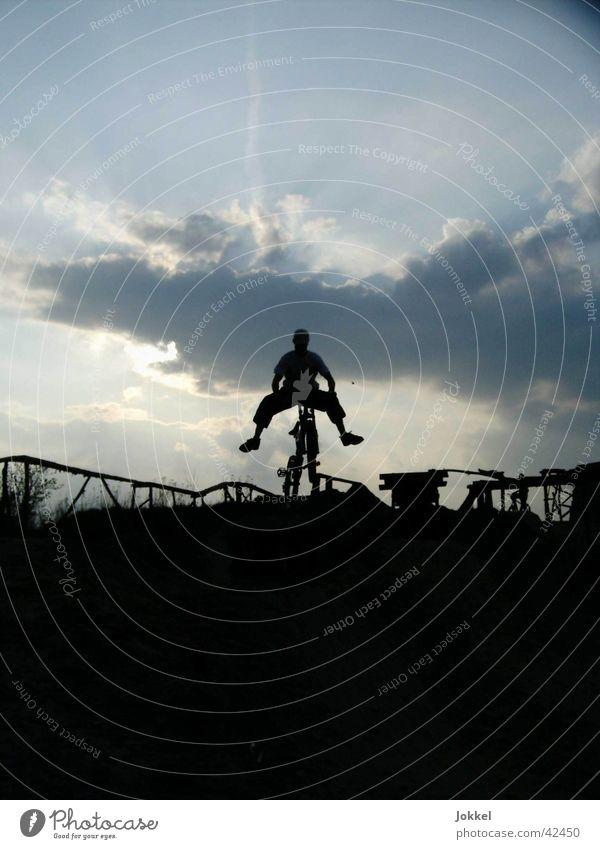Bike in die Nacht Mensch Himmel Wolken dunkel Bewegung springen Fahrrad fahren Mountainbike Trick Funsport Wolkenhimmel Extremsport